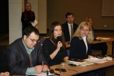 Uczestnicy seminarium siedzą w ławkach. Jedna osoba zabiera głos przez mikrofon.