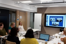 uczestnicy spotkania podczas rozmowy przy stole, na ścianie ekran z wyświetloną prezentacją