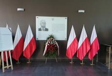 Tablica pamiątkowa w holu KSAP. Pod tablicą wieniec. Po obu stronach tablicy polskie flagi.