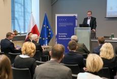 Dyrektor KSAP Wojciech Federczyk przemawia z mównicy w auli KSAP. Widoczni siedzący uczestnicy konferencji. Obok mównicy baner KSAP i flagi polska i unijna.