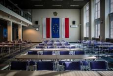 Widok na aule KSAP. Po środku stoją stołu z krzesłami, na ścianie wiszą dwie flag Polski a po środku flaga UE.