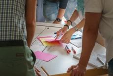 Ludzie stoją oparci o stół, na którym leżą kolorowe karteczki i flamastry.