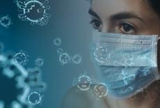 twarz kobiety w masce chirurgicznej, wokół latające cząsteczki wirusa