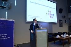Tomasz Janka, Dyrektor RBMP, wygłasza prezentacje stojąc przy mównicy. W tle baner KSAP.