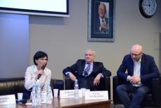 Trzech panelistów siedzi na kanapach, prof. Sylwia Sysko Romańczuk przemawia przez mikrofon.