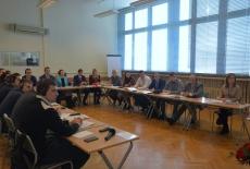Uczestnicy szkolenia siedzą na sali w ławkach.