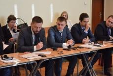 Uczestnicy szkolenia siedzą na sali w ławkach. Jeden z nich mówi trzymając mikrofon.