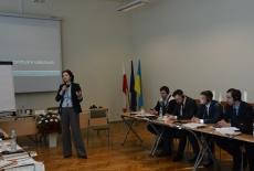 Uczestnicy siedzą na sali, a prowadząca warsztaty Pani Monika Skawińska stoi i prowadzi zajęcia.