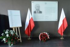 Tablica upamiętniająca Patrona KSAP, po obud stronach stoją polskie flagi, pod tablicą leży wiązanka biało-czerwonych kwiatów. Obok stoi tablica z listą ofiar katastrofy smoleńskiej.