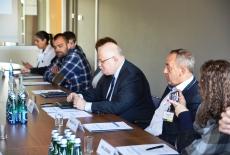 Dyrektor KSAP i zaproszeni dziennikarze siedzą przy stole, mają przed sobą notesy oraz wodę