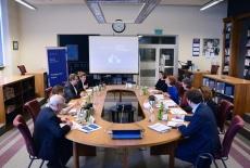 uczestnicy spotkania siedzą przy dużym owalnym stole w bibliotece KSAP