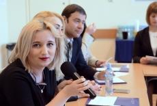 Uczestniczka seminarium mówi do mikrofonu, w tle pozostali uczestnicy. Wszyscy siedzą przy stole.