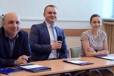 Troje uczestników seminarium siedzi przy stole. Jeden trzyma mikrofon.