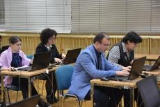 Uczestnicy szkolenia siedzą w ławkach przy komputerach.