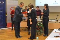 Wojciech Federczyk Dyrektor KSAP wręcza dyplom uczestnitce szkolenia. Za nimi pracownicy KSAP.