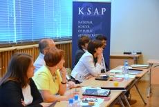 Uczestnicy spotkania siedzą w rzędzie w ławkach po lewej stronie i słuchają wykładu, w tle stoi granatowy roll-up KSAP