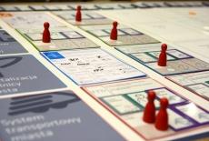 Papierowa plansza z rozstawionymi pionkami do gry i kolorowymi karteczkami.