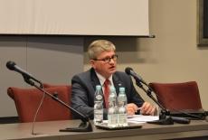 Pan Paweł Soloch siedzi przy stole prezydialnym i mówi do mikrofonu
