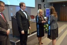 Szef Kancelarii Prezesa Rady Ministrów gratuluje absolwentce KSAP. Obok stoją dyrektor KSAP i Szef Służby Cywilnej.