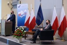 Dyrektor KSAP przy mównicy, Szef Służby Cywilnej siedzi na fotelu. Z tyłu stoją polskie flagi i sztandar KSAP