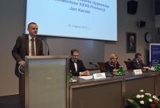 Przy mównicy przemawia prezes Stowarzyszenia Absolwentów KSAP. Obok przy stole prezydialnym siedzą Dyrektor KSAP, Szef Kancelarii Prezesa Rady Ministrów i Szef Służby Cywilnej.