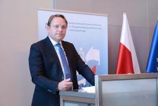 komisarz przy mównicy, w tle flagi polska i unijna