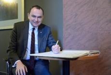 Minister Adam Kwiatkowski podpisuje księgę pamiątkową