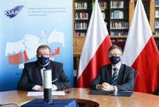 Dyrektor KSAP i Szef Służby Cywilnej podczas konferencji - w bibliotece, na tle polskich flag i baneru KSAP