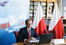 panelista w bibliotece, na tle polskich flag i baneru KSAP