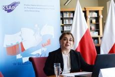 panelistka w bibliotece, na tle polskich flag i baneru KSAP