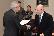 prof. Władysław Stępniak wręcza dyplom uczestnikowi szkolenia. W tle widać pozostałych uczestników.