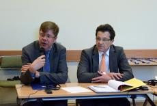 Dwóch uczestników seminarium siedzi przy stole. Jeden z nich mówi do mikrofonu.