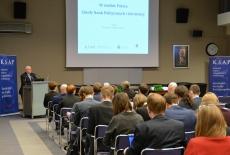 Na Auli KSAP siedzą goście tyłem do obiektywu, a na mównicy przemawia Dyrektor Jan Pastwa