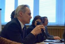 Uczestnik seminarium siedzi przy stole i mówi do mikrofonu. Obok siedzą pozostali uczestnicy.