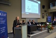 dr Agnieszka Tombińska przemawia przy mównicy, a pozostali paneliści siedzą na kanapach