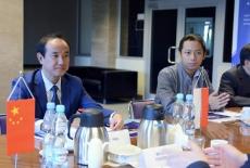 Przedstawiciele chińskiej delegacji siedzą przy stole. Na stole stoją proporczyki - polski i chiński.