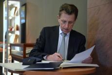 Ambasador Pierre Buhlerwpisuje się do księgi honorowej KSAP