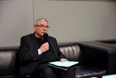 Prof. dr hab. Zbigniew Cieślak siedzi na kanapie i przemawia w prezydium na Auli KSAP
