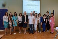 Zdjęcie grupowe uczestników seminarium. W tle na ekranie wyświetlony tytuł seminarium.