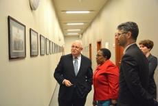 Dyrektor Pastwa stoi przed ścianą ze zdjęciami i pokazuje Pani Ambasador Absolwentów KSAP