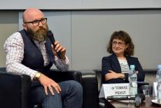 Prelegent dr. Tomasz Piekot trzyma mikrofon i przemawia