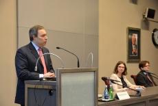 Ambasador Włoch Alessandro de Pedys przemawia przy mównicy. Za stołem prezydialnym siedzą pozostali goście.