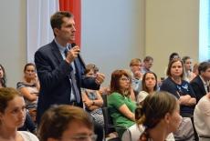 Uczestnik konferencji stoi i mówi do mikrofonu. Obok siedzą inni uczestnicy