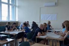 Uczestnicy podczas warsztatów siedzą w grupach i pracują