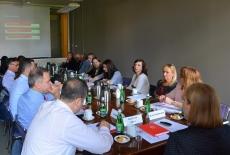 Uczestnicy spotkania siedzą przy dużym prostokątnym stole. W tle na ekranie wyświetlona prezentacja.