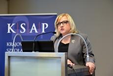 Szef Kancelarii Prezesa Rady Ministrów BEata Kempa przemawia z mównicy w auli KSAP. W tle niebieski baner z logo KSAP.