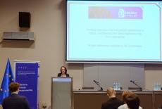 Jedna z finalistek podczas prezentacji przy mównicy. W tle duży ekran z wyświetloną prezentacją.