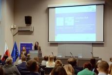 Dwie finalistki podczas prezentacji przy mównicy. W tle duży ekran z wyświetloną prezentacją. Widoczni goście konferencji.
