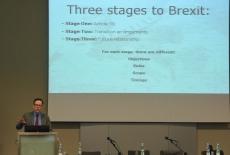 Prowadzący wykład stoi przy mównicy, obok na dużym ekranie wyświetlona prezentacja: Three stages to Brexit