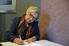 Księgę pamiątkową podpisuje Dyrektor Generalna Kancelarii Prezydenta RP